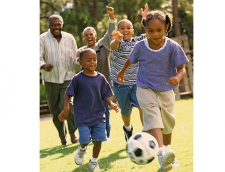 Photo of African American family playing soccer