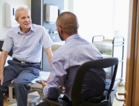 An older man talks with a doctor